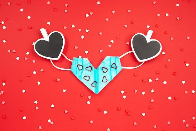 Medizinische maske zum valentinstag und zwei wäscheklammern mit herz