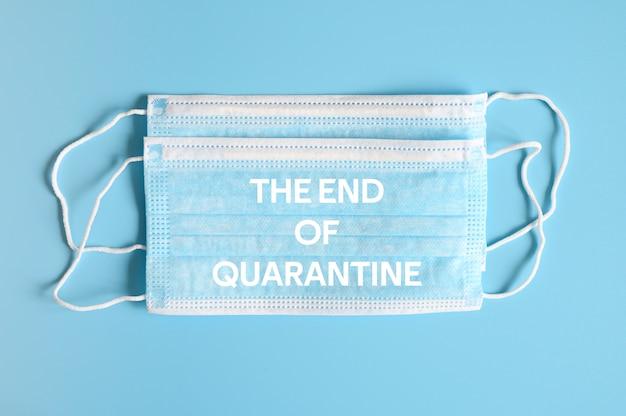 Medizinische masken blaue farbe zum schutz vor bakterien auf blauem hintergrund und text das ende der quarantäne ofl schrift