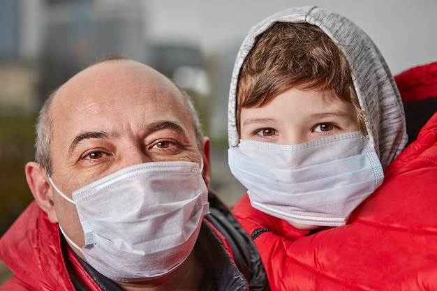 Medizinische masken für männer und kleine jungen auf ihren gesichtern als schutz vor coronavirus.