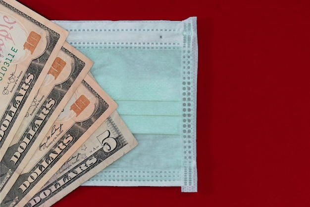 Medizinische masken und dollarnoten als symbol für höhere preise zum schutz der atemwege vor viren. speicherplatz kopieren.