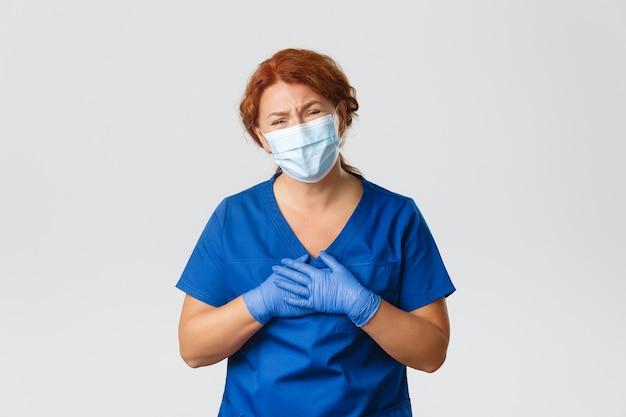 Medizinische mitarbeiter, covid-19-pandemie, coronavirus-konzept. dankbar und berührt, lächelnde rothaarige ärztin, die für die arbeit in der klinik mit virusinfizierten menschen gelobt wird, gesichtsmaske und handschuhe tragen.