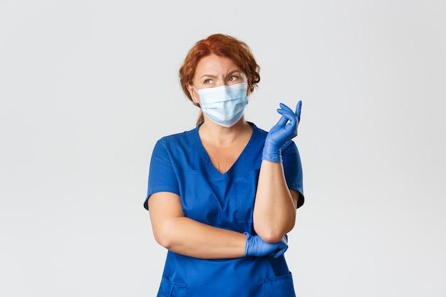 Medizinische mitarbeiter, covid-19-pandemie, coronavirus-konzept. verwirrte und nachdenkliche rothaarige ärztin, krankenschwester in peelings, gesichtsmaske und handschuhen denken, unentschlossen aussehen, wahl oder entscheidung treffen.