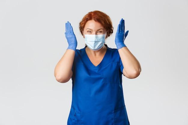 Medizinische mitarbeiter, pandemie, coronavirus-konzept. aufgeregte und glücklich lächelnde ärztin, krankenschwester mittleren alters oder ärztin mit gesichtsmaske und handschuhen, die sich über gute neuigkeiten freuen.