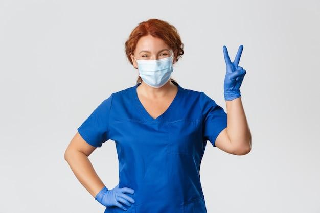 Medizinische mitarbeiter, pandemie, coronavirus-konzept. glücklich lächelnde rothaarige ärztin, krankenschwester, die positiv bleibt, medizinische maske und handschuhe in der klinik tragend, mit patienten arbeitend, friedenszeichen zeigen.