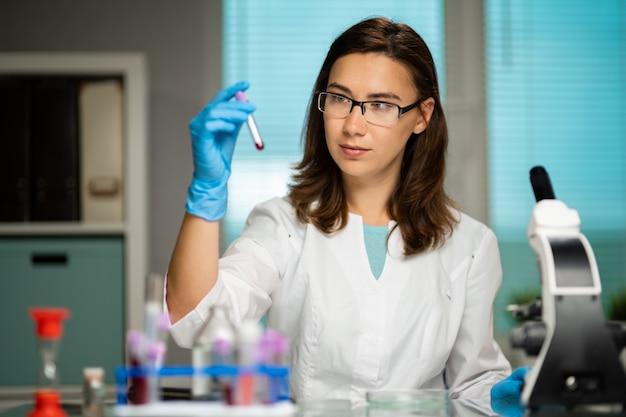 Medizinische mitarbeiterin, die laborforschung mit mikroskop, reagenzgläsern, medikamenten, chemikalien und analysen durchführt, um viren und andere menschliche krankheiten zu untersuchen