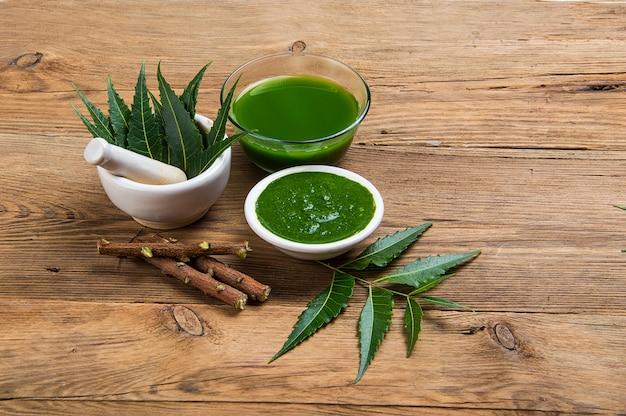 Medizinische neemblätter in mörser und pistill mit neempaste, saft und zweigen auf holztisch
