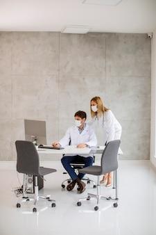 Medizinische paarärzte mit schützenden medizinischen gesichtsmasken, die sprechen und computer im büro benutzen