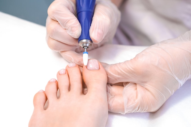 Medizinische pediküre mit einer nagelfeile. fußpeeling im spa mit einem speziellen gerät. klinik für podologie podologie.