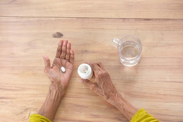 Medizinische pillen der weißen farbe auf handfläche der hand der älteren frauen auf tischoberansicht