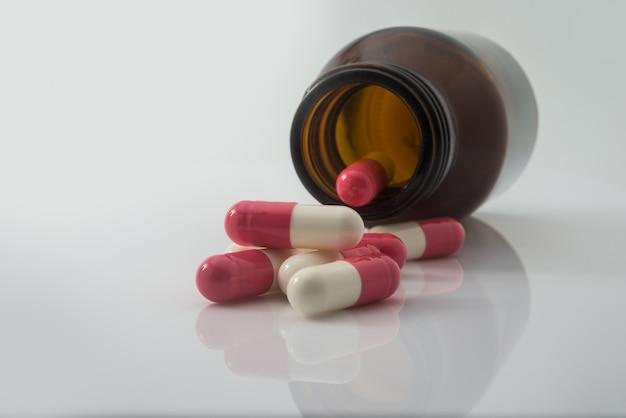 Medizinische pillen, die aus einem gestürzten tablettenfläschchen heraus verschüttet werden