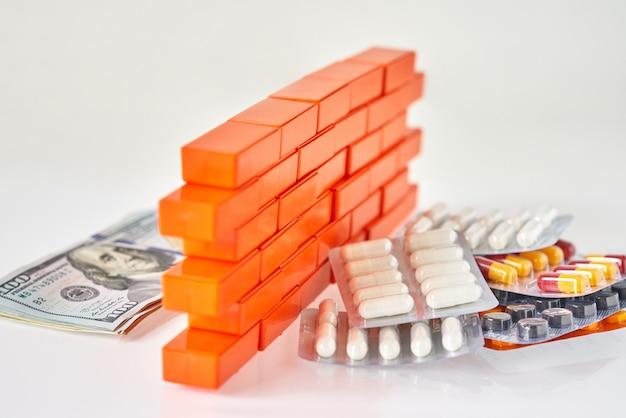 Medizinische pillen und dollarscheingeld trennen sich mit einer spielzeugbacksteinmauer.
