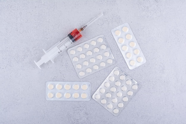 Medizinische pillen und spritze auf marmorhintergrund. foto in hoher qualität