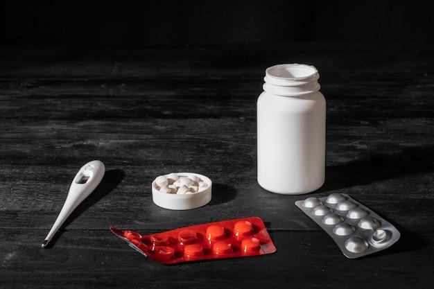 Medizinische pillen und thermometer auf schwarzer holzoberfläche. selbstbehandlungskonzept: minimalistisches zurückhaltendes bild von verschreibungspflichtigen medikamenten.