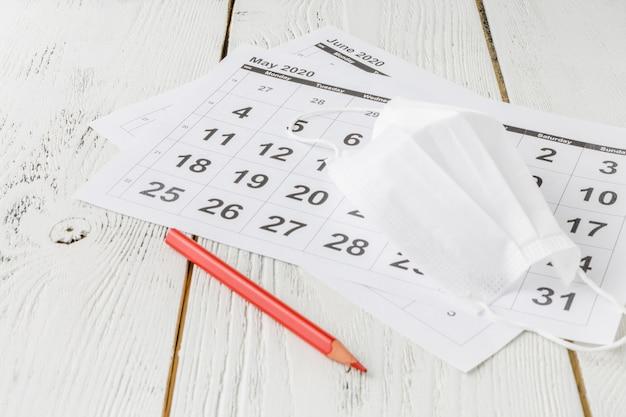 Medizinische schutzmaske auf den kalenderblättern.