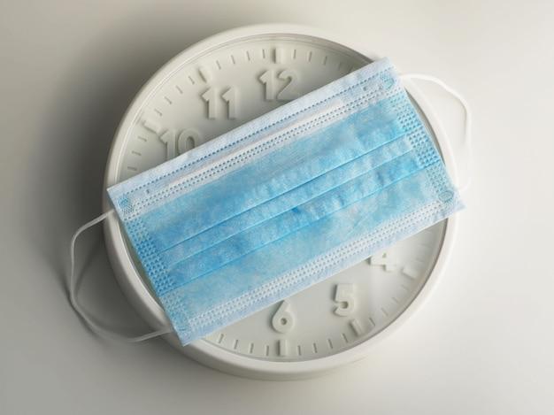Medizinische schutzmaske auf weiße uhr setzen. quarantäne und zeit zu hause zu bleiben.