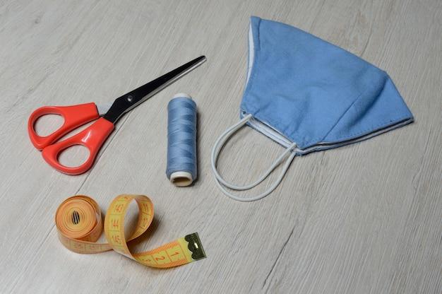 Medizinische schutzmaske blaue farbe, handgefertigt aus textil. antivirale maske, persönliche schutzausrüstung. coronavirus-konzept. Premium Fotos