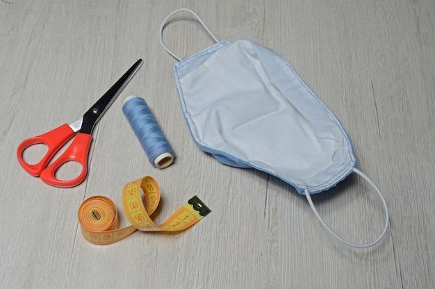 Medizinische schutzmaske blaue farbe, handgefertigt aus textil. antivirale maske, persönliche schutzausrüstung. coronavirus-konzept.