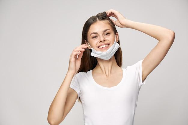 Medizinische schutzmaske in der hand der schönen frau lächelnd