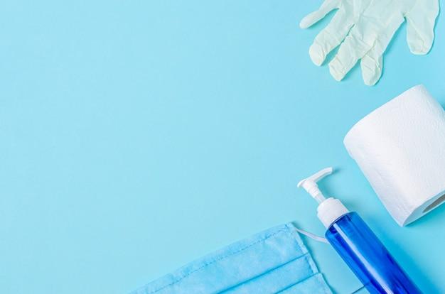 Medizinische schutzmaske, weißer gummihandschuh, toilettenpapier, flasche mit flüssigseife auf blauem hintergrund.