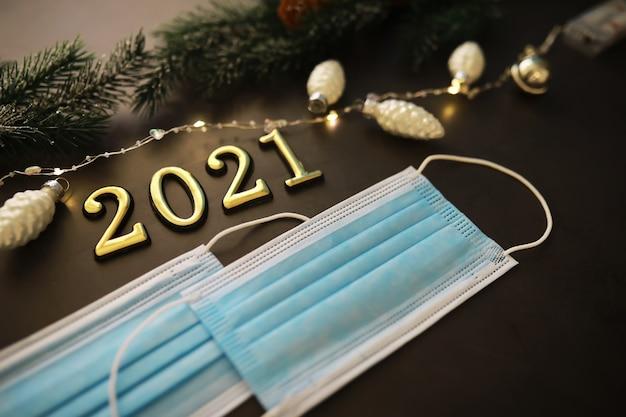 Medizinische schutzmasken auf weihnachtshintergrund mit weihnachtsschmuck. seitenansicht mit platz zum kopieren. das konzept der sicheren feier von weihnachten und neujahr.