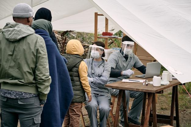 Medizinische spezialisten für schutzmasken, die am tisch im zelt sitzen und den gesundheitszustand von migranten überprüfen, die in der schlange stehen