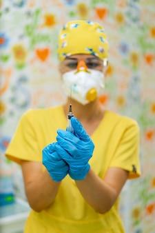 Medizinische spritze in der hand in blauen handschuhen. unscharfer hintergrund der ärztin. injektionskonzept.