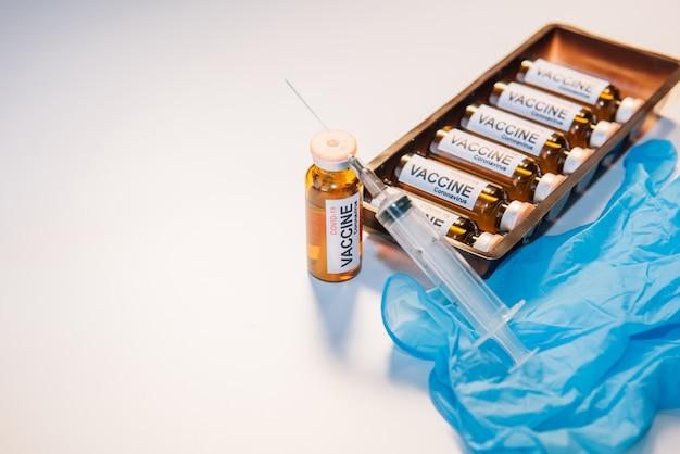 Medizinische spritze und impfstoff in fläschchen, box mit ampullen auf weißem hintergrund mit kopienraum. beschriftung auf dem etikett, nahaufnahme.