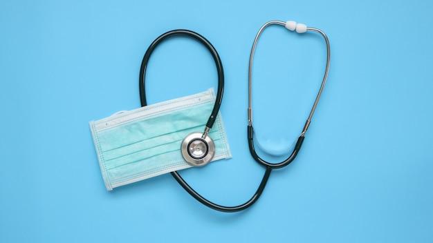 Medizinische stethoskopausrüstung mit chirurgischer gesichtsmaske auf blauem tisch, covid-19 coronavirus-präventions-gesundheitskonzept