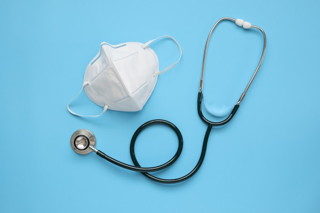 Medizinische stethoskopausrüstung mit kn95-gesichtsmaske auf blauem hintergrund covid-19 coronavirus-präventions-gesundheitskonzept