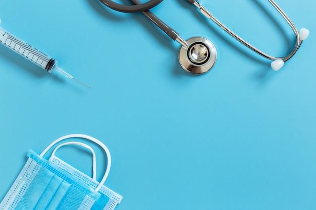 Medizinische stethoskopspritze und hygienemaskenschutzvirus auf blauem tisch.