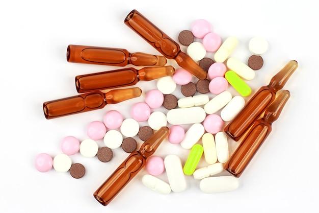 Medizinische tabletten, ampullen für injektionen auf weißem hintergrund. pharmakologie, medizin und behandlung von krankheiten