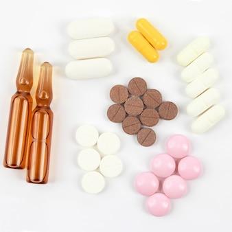 Medizinische tabletten, ampullen für injektionen auf weißem hintergrund. pharmakologie und medizinische industrie