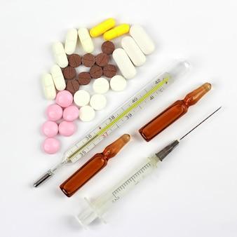Medizinische tabletten, ampullen für injektionen, thermometer, spritze auf weißem hintergrund. pharmakologie und medizinische industrie