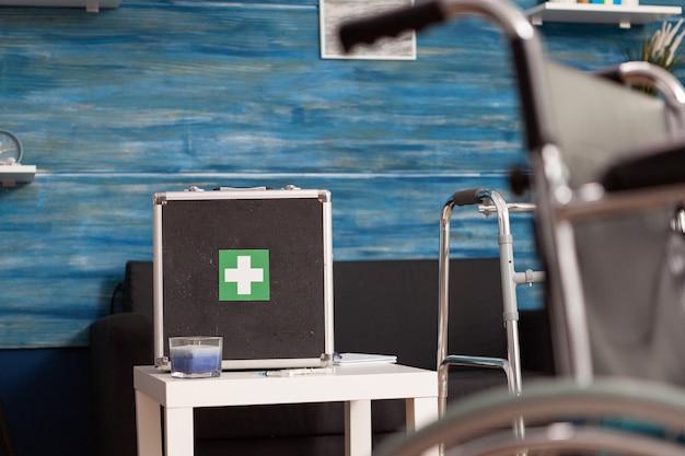 Medizinische taschenausrüstung des krankenhauses, die auf dem tisch im leeren wohnzimmer mit niemandem darin steht