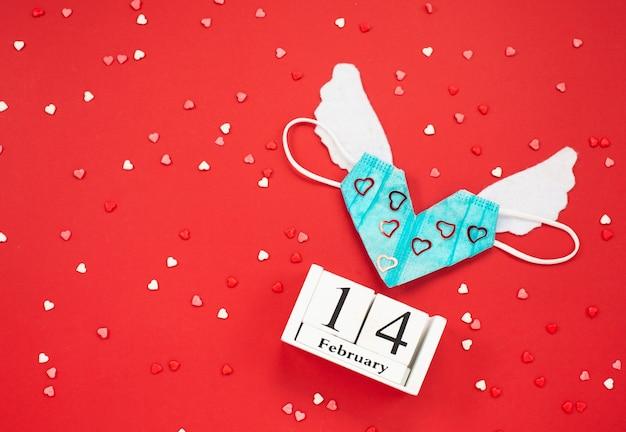 Medizinische valentinsmaske mit weißen flügeln und hölzerner kalendershow vom 14. februar