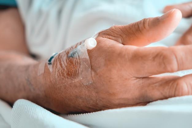 Medizinische versorgung, nahaufnahmebild des iv-tropfens in der hand des patienten im krankenhaus.