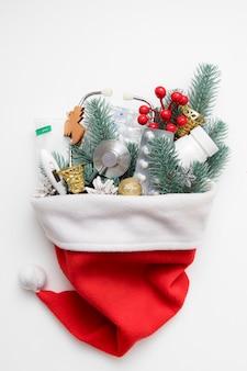 Medizinische weihnachtswohnung lag mit weihnachtsmütze und einem stethoskop, pillen, thermometer auf weißem hintergrund.
