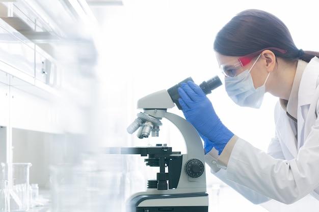 Medizinische wissenschaftlerin mit mikroskop