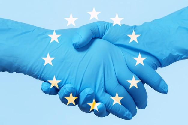 Medizinische zusammenarbeit in der europäischen union. leute, die latexhandschuhe tragen, begrüßen sich.