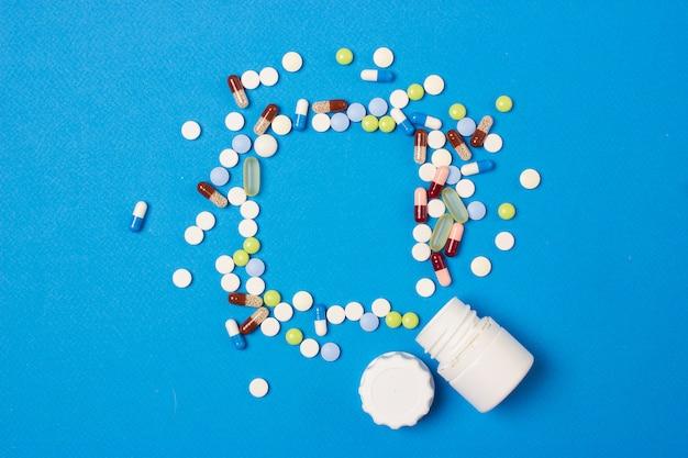 Medizinischer blauer hintergrund mit farbpillen, pillen und kapseln für ein dia oder eine präsentation