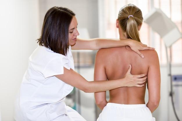 Medizinischer check an der schulter in einem physiotherapie-zentrum.