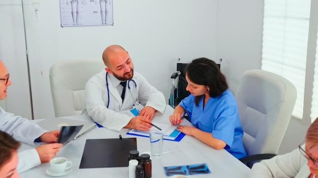 Medizinischer experte im gespräch mit medizinischem personal während eines treffens im gesundheitswesen im konferenzraum des krankenhauses, der röntgenaufnahmen erklärt. kliniktherapeut im gespräch mit kollegen über krankheit, mediziner