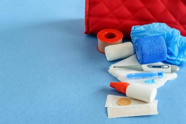 Medizinischer fall mit erste-hilfe-kit-nahaufnahme auf blauer, flacher lage.