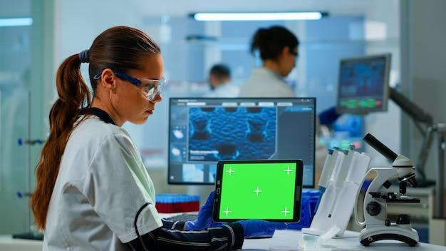 Medizinischer forscher, der an tablet mit green-screen-mock-up-vorlage im labor für angewandte wissenschaften arbeitet. ingenieure, die im hintergrund experimente durchführen und die entwicklung von impfstoffen mit hightech untersuchen