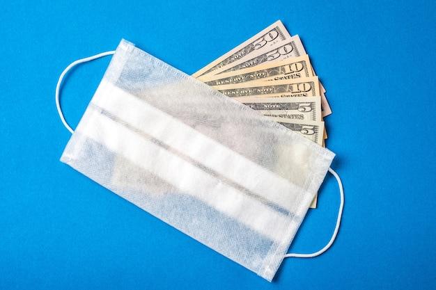 Medizinischer gesichtsschutz auf amerikanischem geld. finanzkrisenkonzept