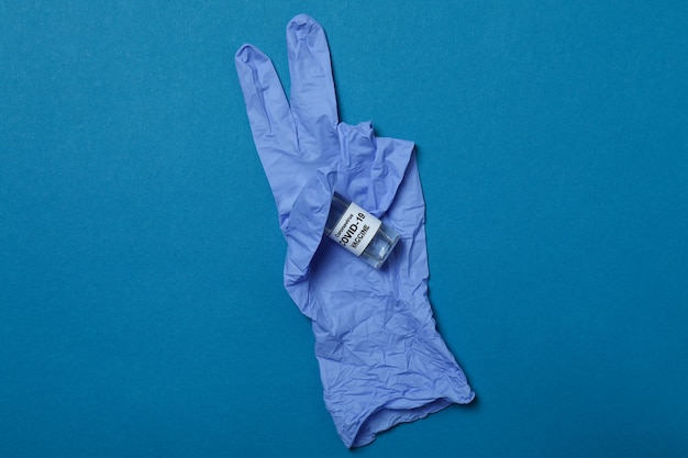 Medizinischer handschuh mit impfstoff auf blauem isoliertem hintergrund