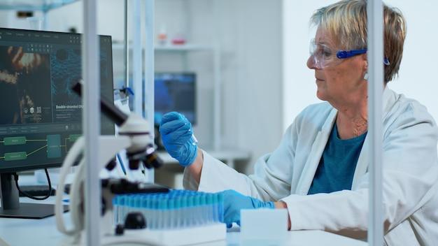 Medizinischer labormitarbeiter, der blutserum analysiert und virustests in einem modern ausgestatteten labor durchführt. multiethnisches team untersucht die entwicklung von impfstoffen mit hightech für die behandlungsentwicklung gegen covid19