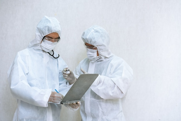 Medizinischer labortechniker mit chemischer schutzkleidung, die im labor den covid-19-impfstoff coronavirus hält