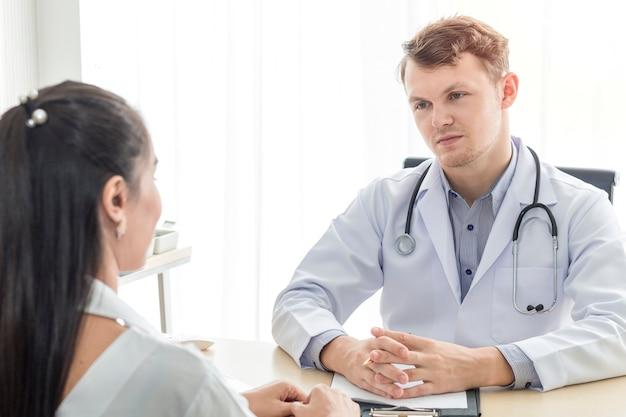 Medizinischer mann, der den jungen patienten der jungen frau versichert und spricht.