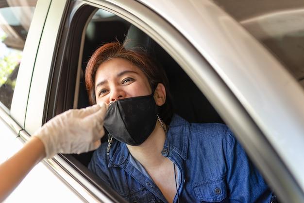 Medizinischer mitarbeiter, der von einer frau im auto einen nasenabstrich nimmt, um auf eine covid19-infektion zu testen